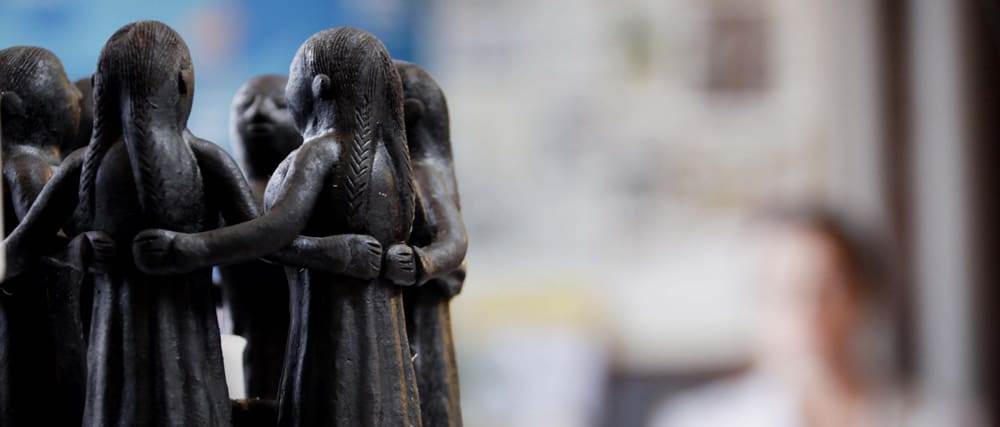 Small statue of a circle of women linking arms.