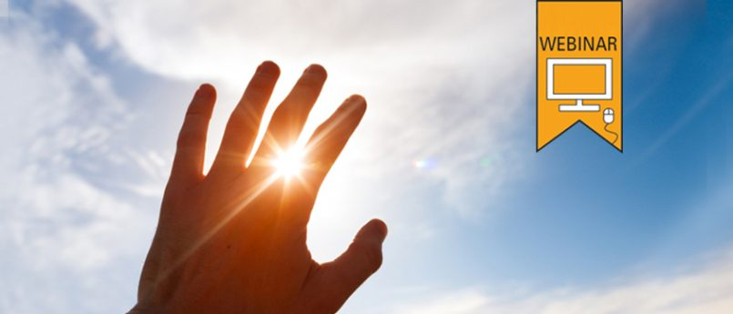 Photograph of a hand being held up to the sun, with light shining between the fingers.